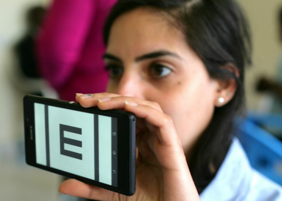 Woman holding up a phone showing Peek Acuity vision check app